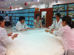 Helping the local women stretch a layer of silk to make a quilt., Julie - June 2012