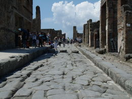 Pompeii tour. 2000 years ago they already had wheel ruts ground into the stone roads. Those 3 stones you see are equivalent to speed bumps, as almost all of Pompeii is on a slope. , Papa Harold - July 2013