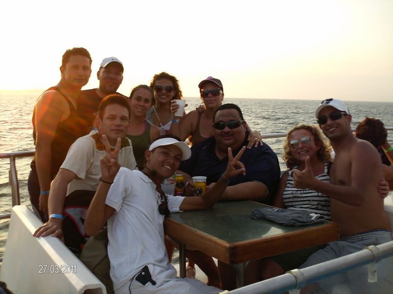 My husband and me having fun with a group of local people on the boat, drinking and eating fantastic pineapple
