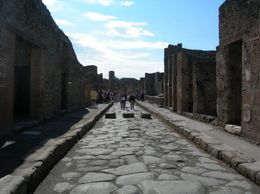 This is one of the roads in Pompeii showing buildings on each side and the rocks that the road was made from., Lyn C - October 2008
