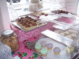 There is tray after tray of yummy cupcakes. They even have Carrie`s cupcake which has pink frosting and a small flower in the corner of the cupcake., LYNN S - June 2010