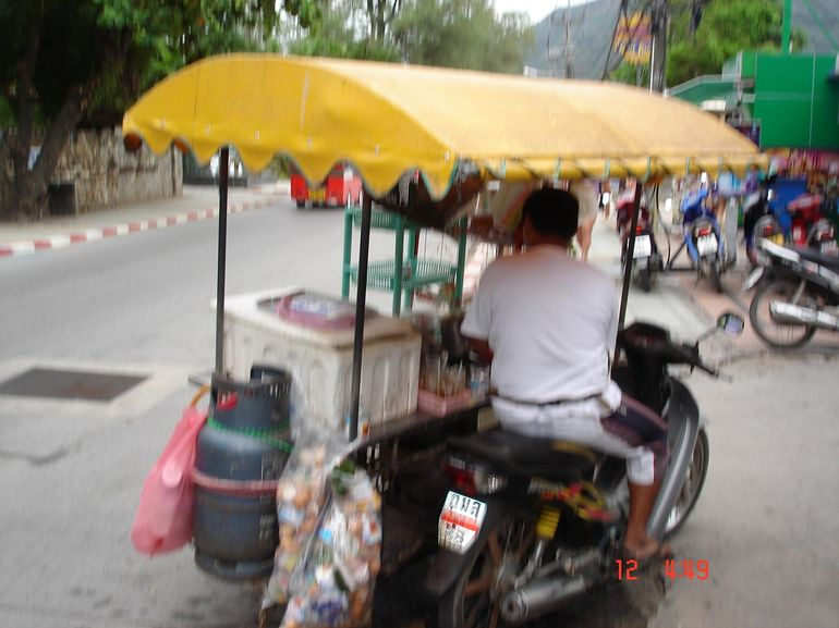 People had home made carts on the side of their cars as income. - Phuket