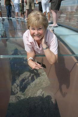 Photo of Las Vegas Ultimate Grand Canyon 4-in-1 Helicopter Tour Sally laying on the glass bottom Skywalk