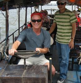 "The ""captain"" of our small boat let me get behind the wheel and steer us down the Mekong River - quite an experience!, Kevin S - July 2010"