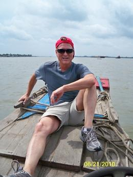 This is a picture of me sitting on the bow of the boat with the Mekong River behind me., Kevin S - July 2010