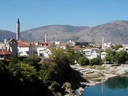 A view across the Neretva River in Mostar, with several mosque minarets in the distance. - October 2007