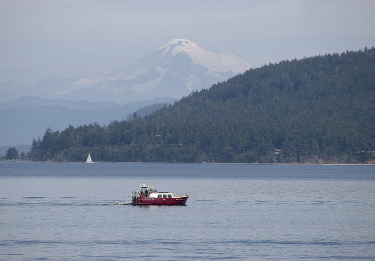 Red boat on Puget Sound with Mt Baker in background - Seattle