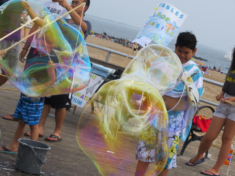 Kids making giant bubbles on the Boardwalk at Coney Island - New York City