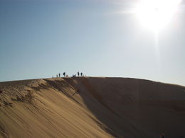 Other tourists stand on the sand dune preparing to slide down. , Ericka M - November 2015