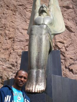 My fiance standing in front of the statue of those who died at the building of Hoover Dam. I heard if you rub the feet its good luck., Jasmine .T - April 2009