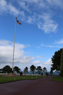 The flag waves over the field of crosses ... American Cemetery at Normandy. , John C - September 2012