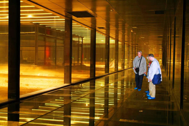 Walking on the glass walkway where you can see the excavated figures and the process below