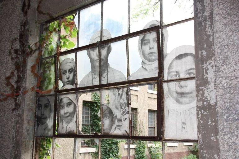 Inside of the hospital. This is a view of windows on the hall way enhanced by an artist rendition of some of the immigrants coming to be cared for at the hospital