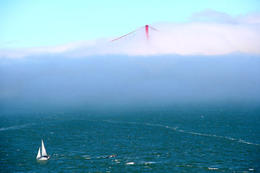 The top of the Golden Gate Bridge is just peeping through the fog on a beautiful San Francisco day. A yacht sails past Alcatraz Island in the foreground. , Peter Whitten - March 2011