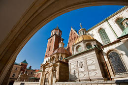 Photo of   Wawel Cathedral in Krakow viewed from behind a gothic arch