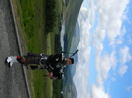 An englishman wearing scottish kilt blowing pipe at one of the lochs on our tour , pug - June 2013
