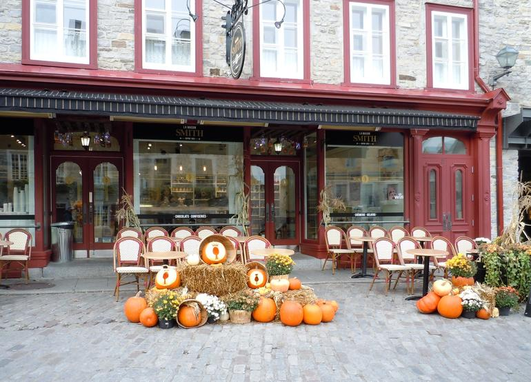 A shopkeeper in Petit Champlain welcomes fall visitors to his place. - Quebec City
