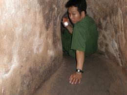 One of the tunnel guides at the Cu Chi Tunnels guides you through. The tunnels are actually pitch black apart from the guiding torch, the flash just makes it look bright., Justin L - January 2009