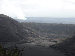 Kilauea smoking in the background and Kilauea iki crater in the foreground. Walkers just visible on the crater floor. I was wishing we had time to join them. , PATRICIA C - June 2011