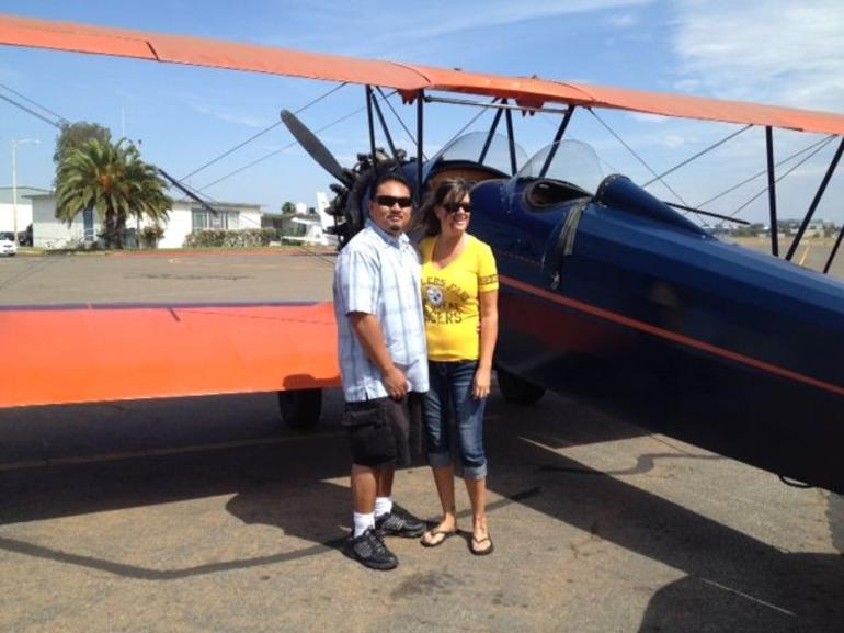 Cindy and Randy standing next to our 1927 plane - San Diego