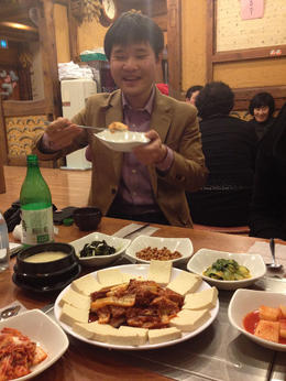 Our tour guide, Jason, demonstrates how to stack tofu, kimchi and pork as we dine at Dubuchon. - May 2013