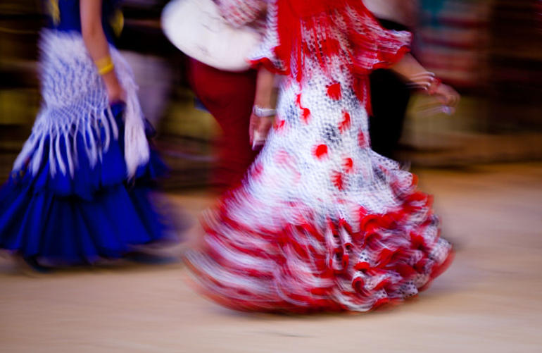 Two women walking in traditional Spanish Flamenco dresses during Feria de Abril, Seville