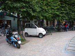 The ratio of autos to bikes is seen as these vehicles are parked on the sidewalk. , Arlene D - October 2013