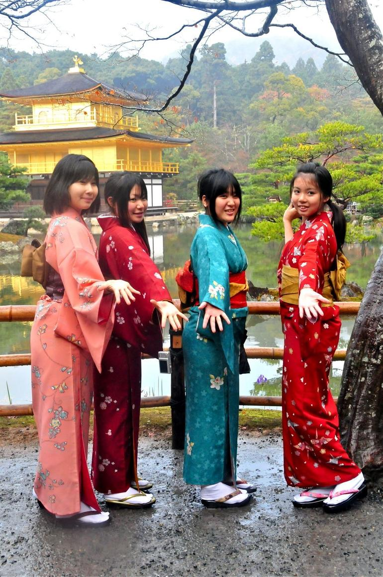 Four young Students in Kimonos pose for their friends in front of the Golden pavilion, to the delight of an old photographer looking for interesting variations to the standard tour shot.