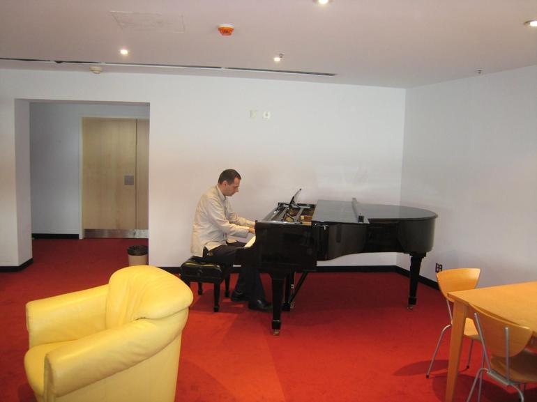 Our guide playing the piano in the dressing room - Sydney