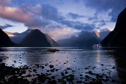 Ferry heading out into Milford Sound, New Zealand, as the clouds and mountain tops start to light up by the rising sun - December 2011