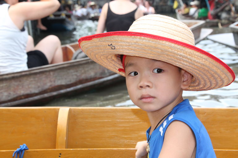 A boy in a long tailed boat. - Bangkok