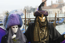 Wearing carnival masks, San Giorgio Maggiore church in the background, Venice, Italy - May 2011