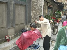 Someone having a hair cut in a street market in China., JULIE F - March 2008