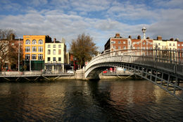 Dublin landmark - Ha'penny Bridge on Liffey River. Rows of colorful houses - June 2011