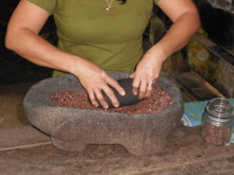 Making chocolate, grounding beans in an old volcanic rock, using a stone from the river. , Alexandru T - December 2013