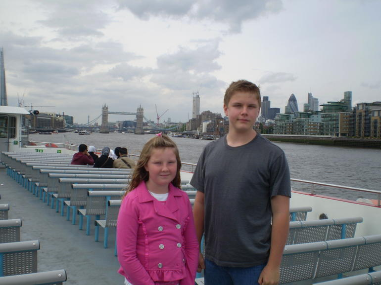 kids on river boat tower bridge in background - London