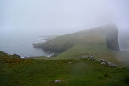 Neist point in Skye, covered in mist and rain. This is the view from pretty much the parking lot, as we were not able to venture any further due to the wind and storm. , Anita B - June 2016