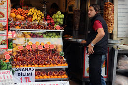 A vendor stands near his stall serving freshly squeezed orange and pomergrenate juice and donor kebabs , Prezzman - June 2014