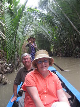 My wife and I enjoying being rowed along a tributary of the Mekong River in a long tail boat. The women who row these boats were exceptionally skilled . , Warwick B - May 2011