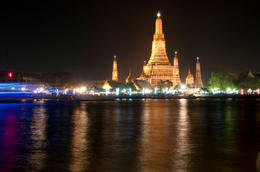 On Chao phraya River: Wat Arun (Temple of the Dawn) Illuminated in the evening in Bangkok, Thailand - June 2011