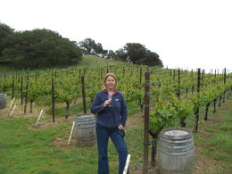 Mrs G enjoying a glass next to the grape vines , Donna G - April 2014
