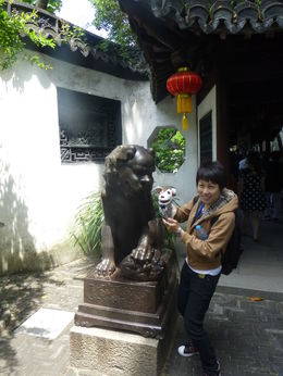 Mary and Sock Puppet posing with a female lion at the Yuyuan Garden in Shanghai. She loved Sock Puppet, and used him to help her guide our entire tour! , Jamey F - May 2015