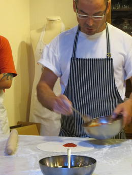 Giovanni, the chef, showing us how do put the sauce on the pizza dough. He was an great teacher! , Connie C - June 2012