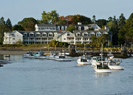 Coastal scenic at sunset with hotel and fishing boat on a bay marina (Kennebunkport, Maine, USA). - May 2011