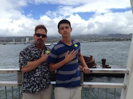 My husband Brian and my son Nick with their hands on their hearts because of the heavy hearts felt while visiting the USS Arizona Memorial. , Brian M - October 2014