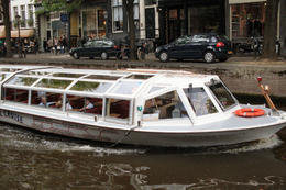 One of the many boats wending their way through the Canals. Our pizza cruise boat was very similar. , Gail W - August 2011