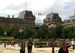 This picture shows it all. Taken in the square outside the entry ton Notre Dame Cathedral. The french arctitecture, the lighting fixtures the flag, the pigeons and the people enjoying their day. , Graeme L - July 2012
