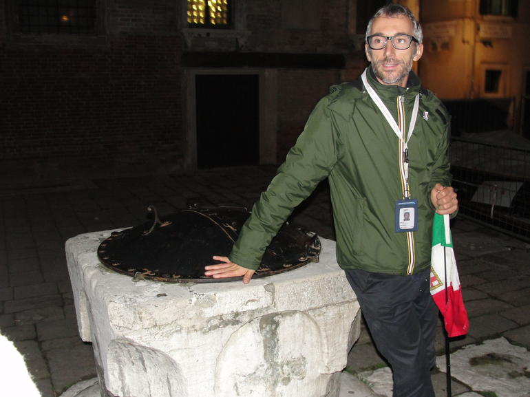 Our guide telling the story of the man found in the well - - Venice