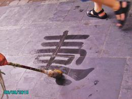A man is writing Chinese characters on the walkway at the Summer Palace. - August 2010