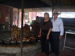My parents taking a photo in front of the Asado. Part of the luncheon food given to us later on during the day., Georgia H - November 2009
